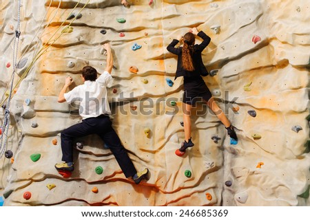 Competition between business partners on man-made cliff in the sport centre
