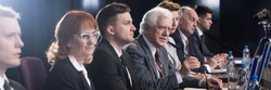 Competition between politician during political debate before election. Older confident man in suit speaking to microphone