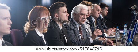 Shutterstock Competition between politician during political debate before election. Older confident man in suit speaking to microphone