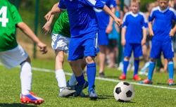 Competition between two youth soccer teams. Boys in blue and green sport uniforms running and kicking soccer ball on a pitch.
