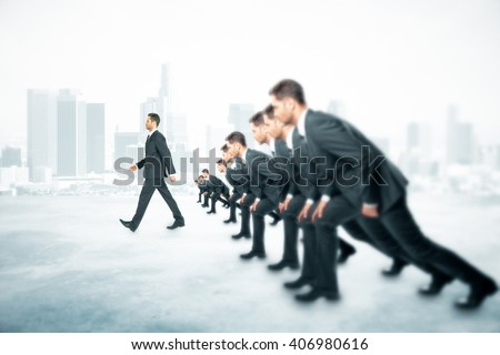 Competition concept with many businessmen about to run and one walking ahead of them on foggy city background