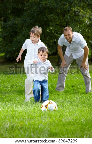 Competition of two little brothers in football in a summer garden