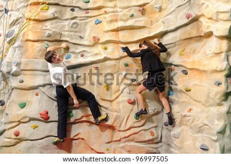 competition of young businesswoman and businessman on rock wall in sport center