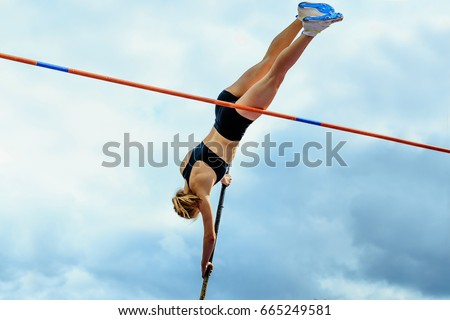 competition pole vault jumper female on blue sky background #665249581