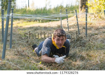 Competitions for endurance. The man crawls under the rope. Marsh throw #1179328276