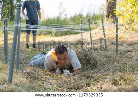 Competitions for endurance. The man crawls under the rope. Marsh throw #1179329335