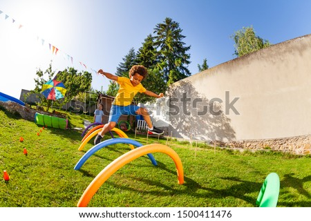 Competitive active game - boy jump over obstacles Stock photo ©