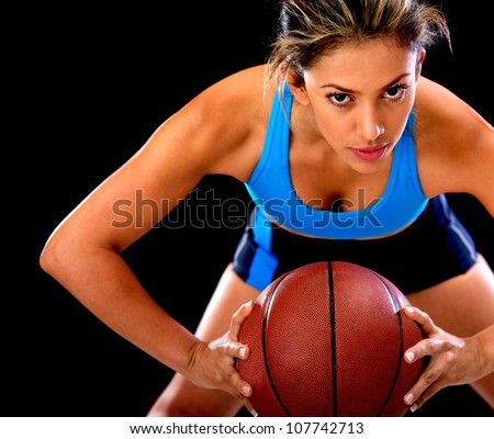 Competitive basketball player holding the ball - isolated over black background