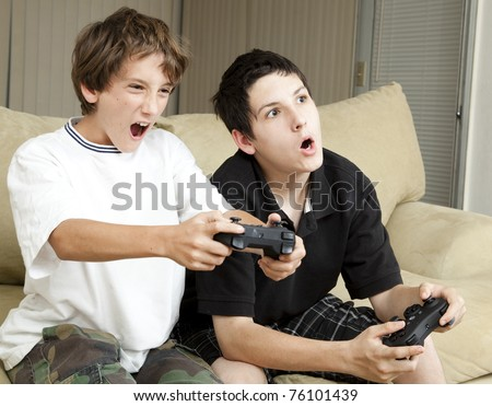 Competitive brothers playing video games at home.