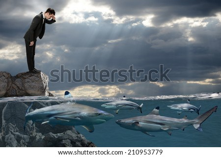 Competitive business concept with businessman looking at sharks swimming in ocean