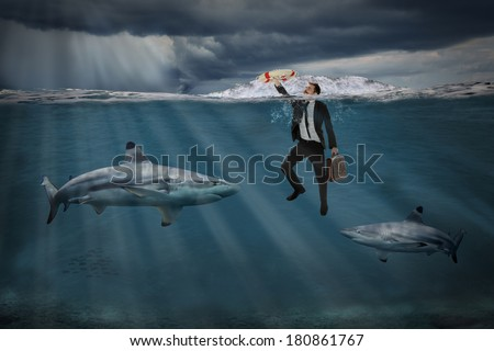 Competitive business concept with businessman swimming among sharks in stormy seas