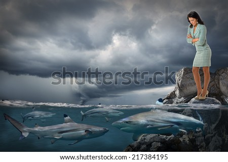 Stock Photo Competitive business concept with businesswoman looking at sharks swimming in ocean