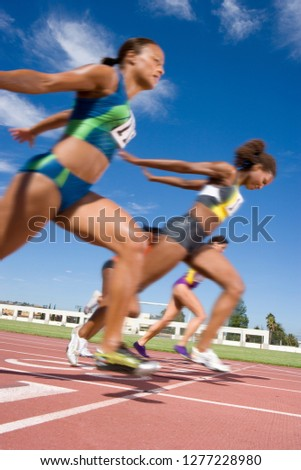 Competitive female athletes crossing finishing line sprint race