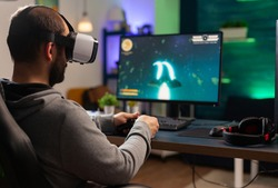 Competitive gamer playing e-sport championship using technology network wireless Professional man wearing vr headset and play online space shooter competition on powerful computer
