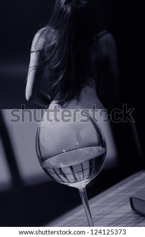 Compilation from two  photos, created by  simple method of imposing. One photo: naked girl, rear view. Second photo: glass with wine, book, on table, against  window/I waited.(About shot borders)