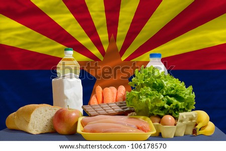 complete american state flag of arizona covers whole frame, waved, crunched and very natural looking. In front plan are fundamental food ingredients for consumers, symbolizing consumerism