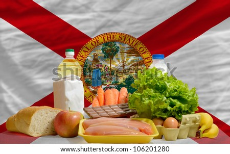 complete american state flag of florida covers whole frame, waved, crunched and very natural looking. In front plan are fundamental food ingredients for consumers, symbolizing consumerism