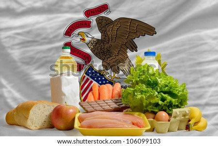 complete american state flag of illinois covers whole frame, waved, crunched and very natural looking. In front plan are fundamental food ingredients for consumers, symbolizing consumerism