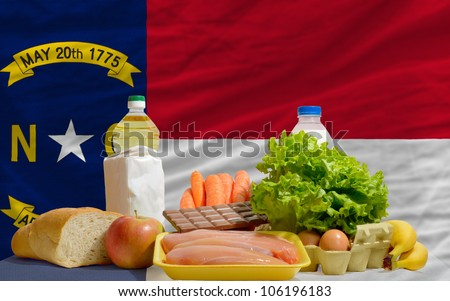 complete american state flag of north carolina covers whole frame, waved, crunched and very natural looking. In front plan are fundamental food ingredients for consumers, symbolizing consumerism