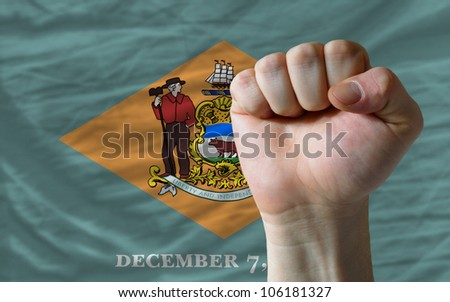 complete american state of delaware flag covers whole frame, waved, crunched and very natural looking. In front plan is clenched fist symbolizing determination