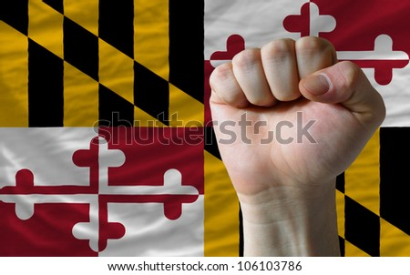 complete american state of maryland flag covers whole frame, waved, crunched and very natural looking. In front plan is clenched fist symbolizing determination