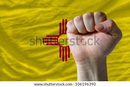 complete american state of new mexico covers whole frame, waved, crunched and very natural looking. In front plan is clenched fist symbolizing determination