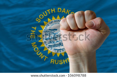 complete american state of south dakota covers whole frame, waved, crunched and very natural looking. In front plan is clenched fist symbolizing determination