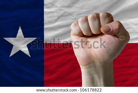 complete american state of texas covers whole frame, waved, crunched and very natural looking. In front plan is clenched fist symbolizing determination