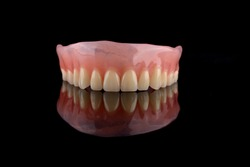Complete denture, full denture close up with black back ground.