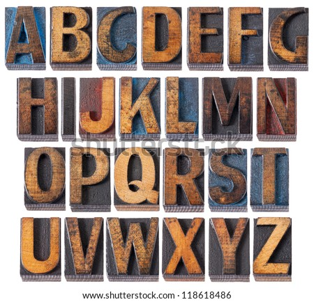 complete English alphabet - collage of 26 isolated vintage wood letterpress printing blocks, scratched and stained by blue, red and black ink