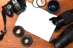 Complete kit for modern digital SLR camera and blank sheet of paper for copyspace. The concept for learning photography. Cover for photo exhibitions, online photo lessons and tutorials