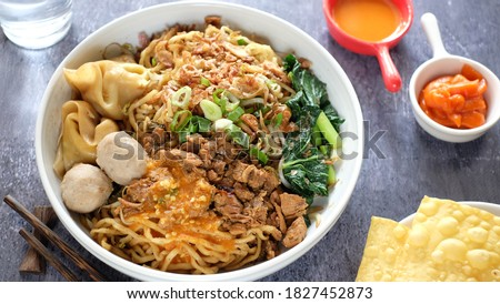 Complete Mie ayam or Mie Yamin or Yamin Noodle with chicken meat, vegetable, Pangsit Goreng, Pangsit rebus and meat ball on white plate.   Zdjęcia stock ©