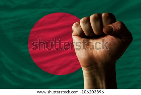 complete national flag of bangladesh covers whole frame, waved, crunched and very natural looking. In front plan is clenched fist symbolizing determination