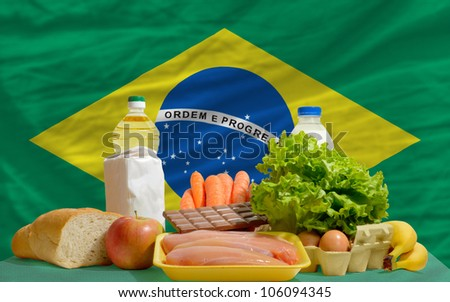 complete national flag of brazil covers whole frame, waved, crunched and very natural looking. In front plan are fundamental food ingredients for consumers, symbolizing consumerism an human needs