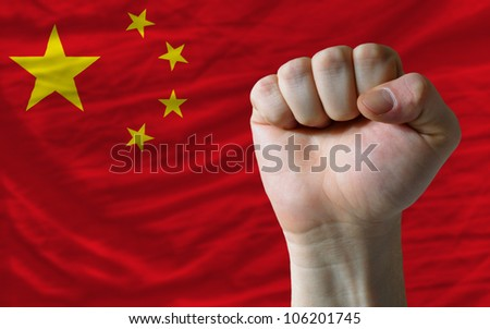 complete national flag of china covers whole frame, waved, crunched and very natural looking. In front plan is clenched fist symbolizing determination