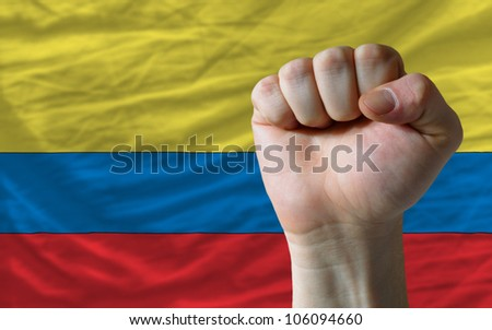 complete national flag of colombia covers whole frame, waved, crunched and very natural looking. In front plan is clenched fist symbolizing determination
