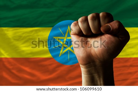 complete national flag of ethiopia covers whole frame, waved, crunched and very natural looking. In front plan is clenched fist symbolizing determination