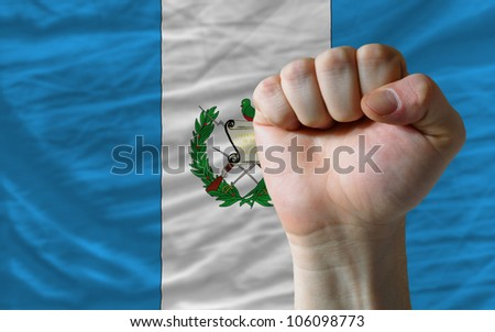 complete national flag of guatemala covers whole frame, waved, crunched and very natural looking. In front plan is clenched fist symbolizing determination