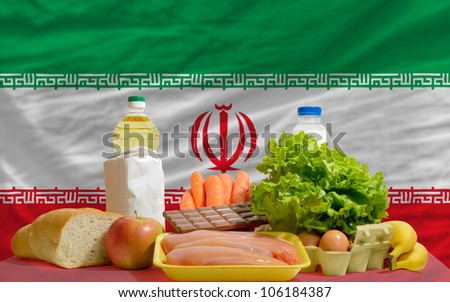 complete national flag of iran covers whole frame, waved, crunched and very natural looking. In front plan are fundamental food ingredients for consumers, symbolizing consumerism