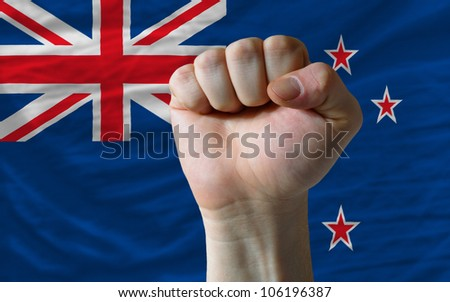 complete national flag of new zealand covers whole frame, waved, crunched and very natural looking. In front plan is clenched fist symbolizing determination