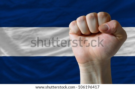 complete national flag of nicaragua covers whole frame, waved, crunched and very natural looking. In front plan is clenched fist symbolizing determination
