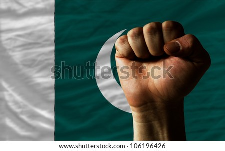 complete national flag of pakistan covers whole frame, waved, crunched and very natural looking. In front plan is clenched fist symbolizing determination