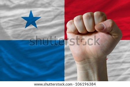 complete national flag of panama covers whole frame, waved, crunched and very natural looking. In front plan is clenched fist symbolizing determination
