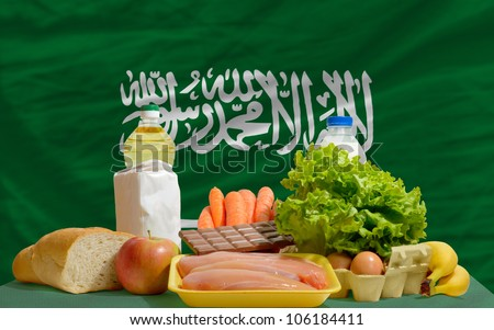 complete national flag of saudi arabia covers whole frame, waved, crunched and very natural looking. In front plan are fundamental food ingredients for consumers, symbolizing consumerism