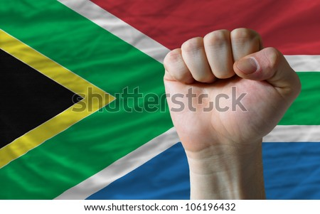 complete national flag of south africa covers whole frame, waved, crunched and very natural looking. In front plan is clenched fist symbolizing determination