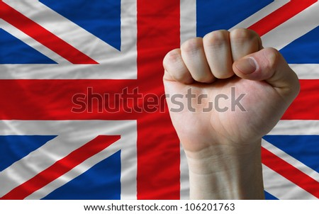 complete national flag of uk covers whole frame, waved, crunched and very natural looking. In front plan is clenched fist symbolizing determination
