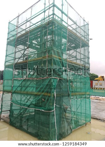 Complete scaffold with netting and green tag approval for access used and for construction of r.c column. Image contain excessive noise, film grain, compression artifacts and posterization. Photo stock ©