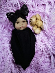 Completely realistic ethnic newborn baby doll in black set