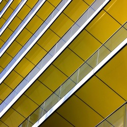 Complex building structural detail, yellow metal bars and glass
