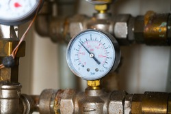 Complex piping system with hot analog pressure gauge with dust, dirt, dirty stains. water manifold with manometer and pressure control valve